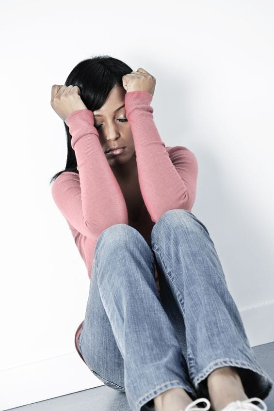 8264789 – depressed black woman sitting against wall on floor with eyes closed